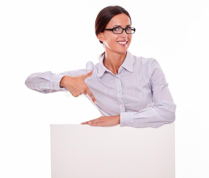 指向有招贴的微笑的深色的妇女 免版税库存照片