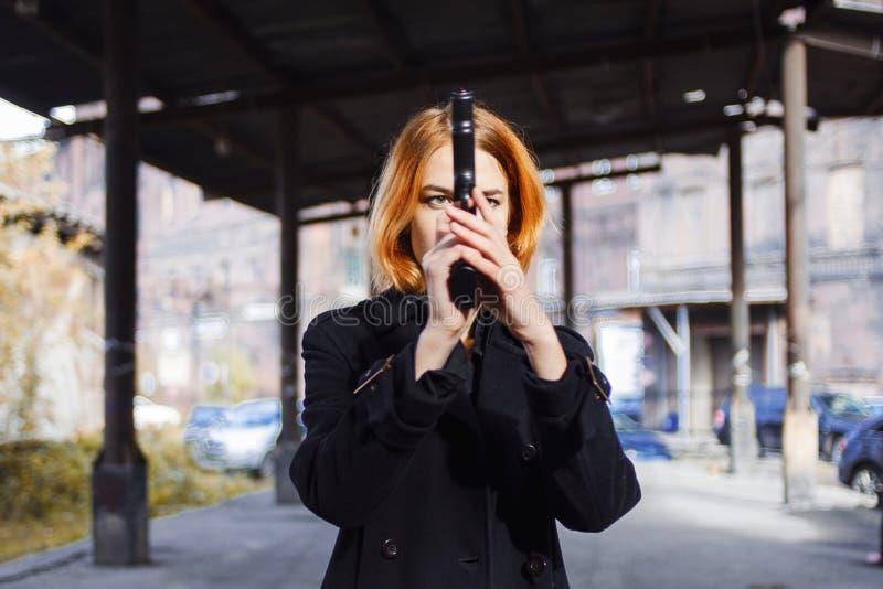 指向枪的妇女 黑手党在某人的女孩射击在街道上 免版税图库摄影