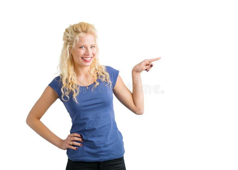 指向某事的妇女与她手指和微笑 免版税库存图片