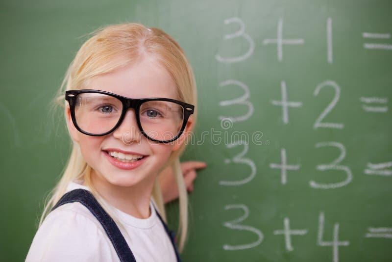 指向某事的微笑的聪明的女小学生 库存照片