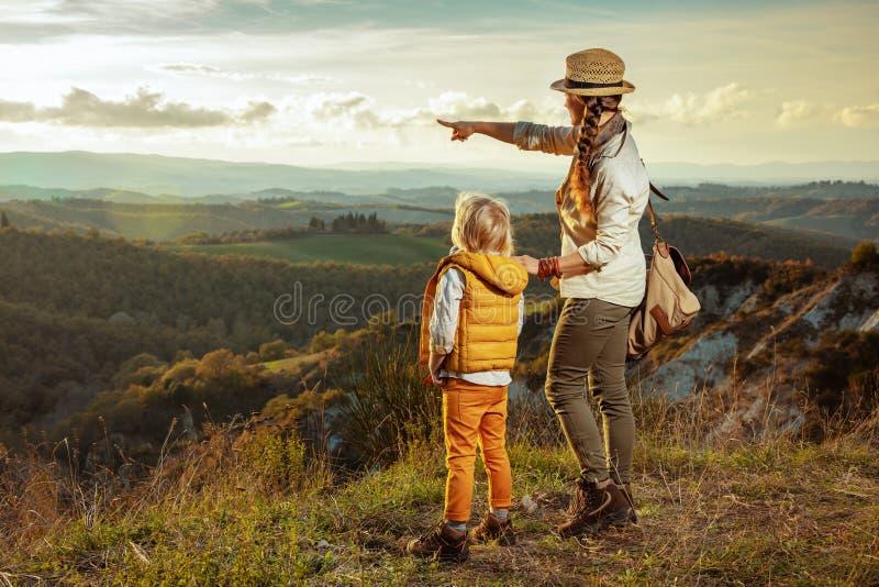 指向某事的现代母亲和儿童徒步旅行者 免版税库存照片