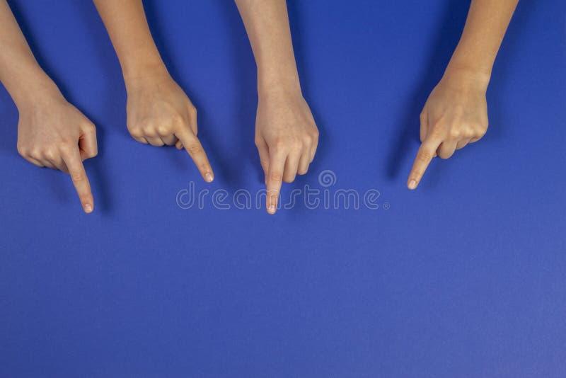 指向某事的许多孩子手在蓝色背景 免版税库存照片