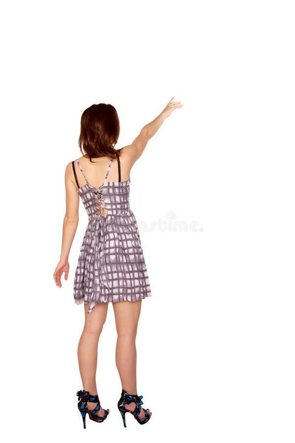 指向某事的青少年的女孩。 背面图。 库存照片