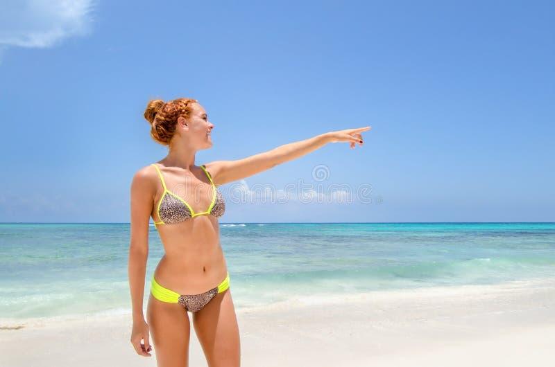 指向海滩的少妇 库存照片