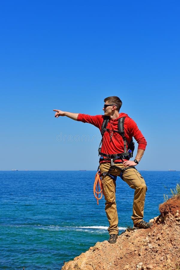 指向海洋的登山人 免版税库存图片