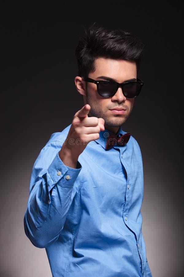 指向照相机的严肃的看起来的年轻男性 免版税库存图片