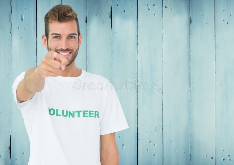 指向照相机的微笑的男性志愿者 库存图片
