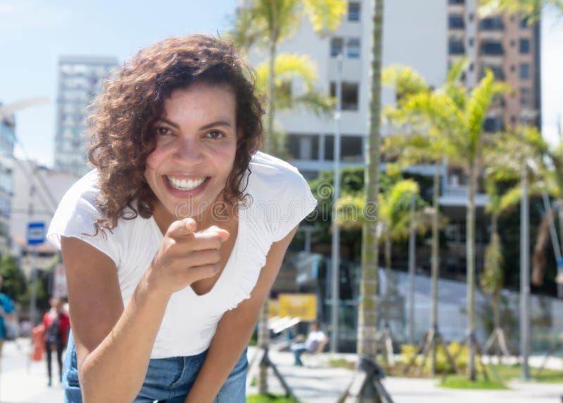 指向照相机的美丽的西班牙妇女 免版税图库摄影