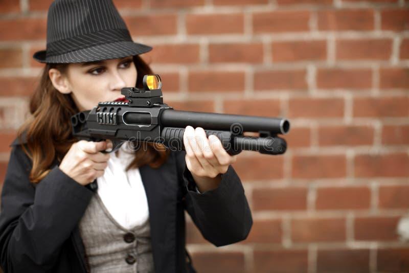 指向猎枪时髦的妇女 免版税库存图片