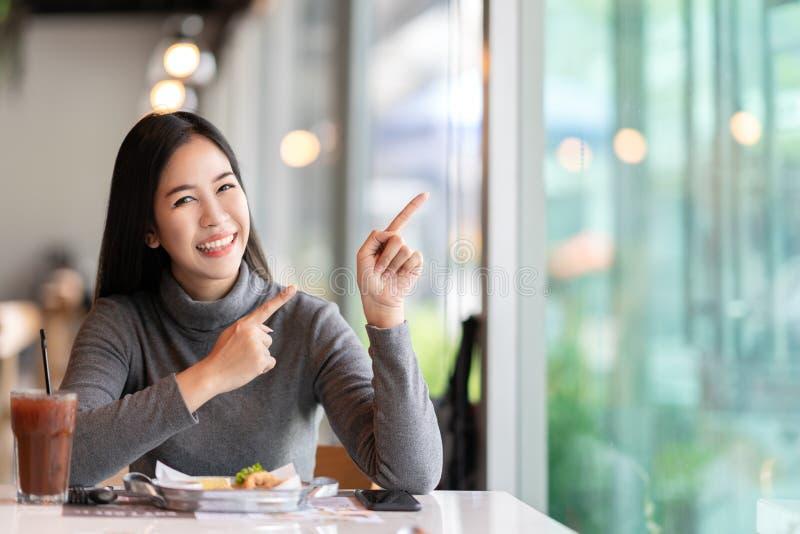 指向由显示的感觉愉快的消息边决定的年轻可爱的亚裔妇女惊奇咖啡馆 免版税库存图片