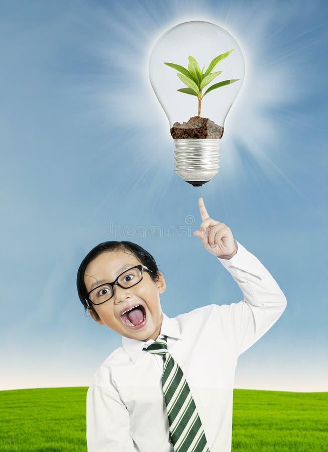 指向电灯泡的男孩 免版税库存图片