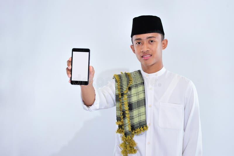 指向白色屏幕手机的一个微笑的年轻回教人的画象 免版税库存照片