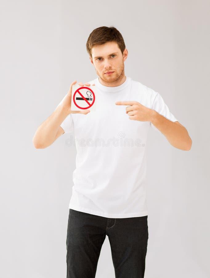 指向禁烟标志的年轻人 图库摄影