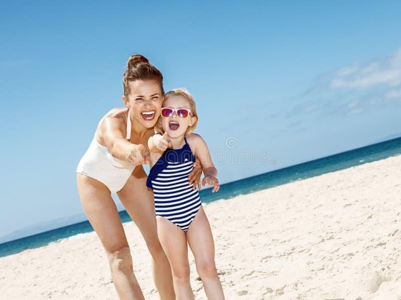 指向秘密审议的微笑的母亲和孩子沙滩 免版税库存图片