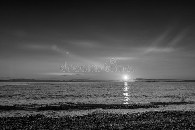 指向罗伯特日落在海滩的月光 免版税库存图片