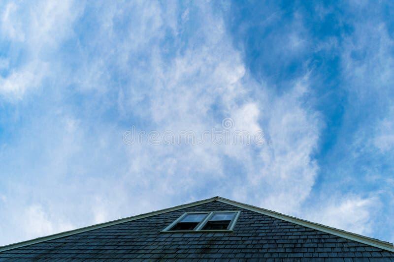 指向美丽的蓝色,有一点多云天空,石块海岛,RI的三角屋顶 图库摄影