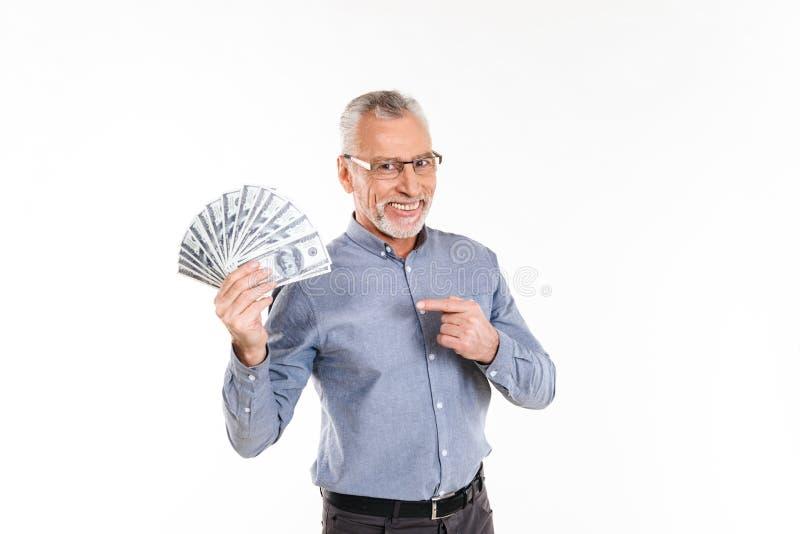 指向美元的老微笑的人在手中举行 免版税库存图片
