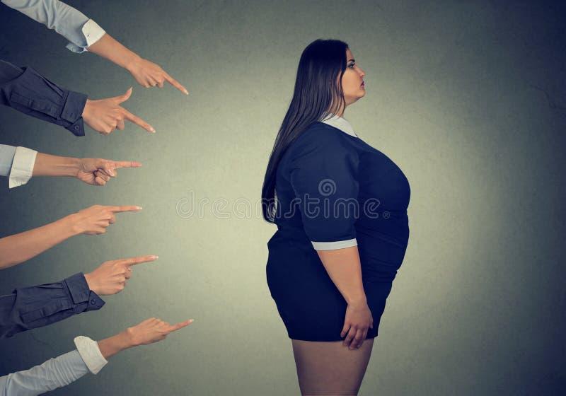 指向肥胖妇女的许多手指 免版税库存图片