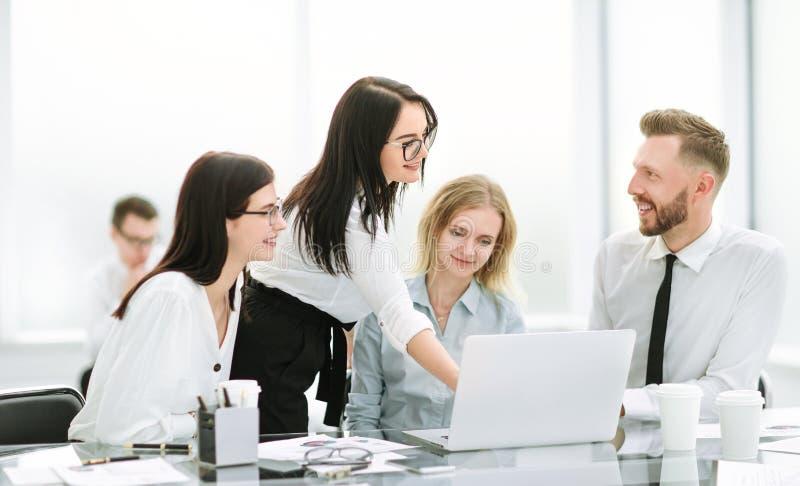 指向膝上型计算机屏幕的女实业家在与企业队的一次会议期间 免版税图库摄影