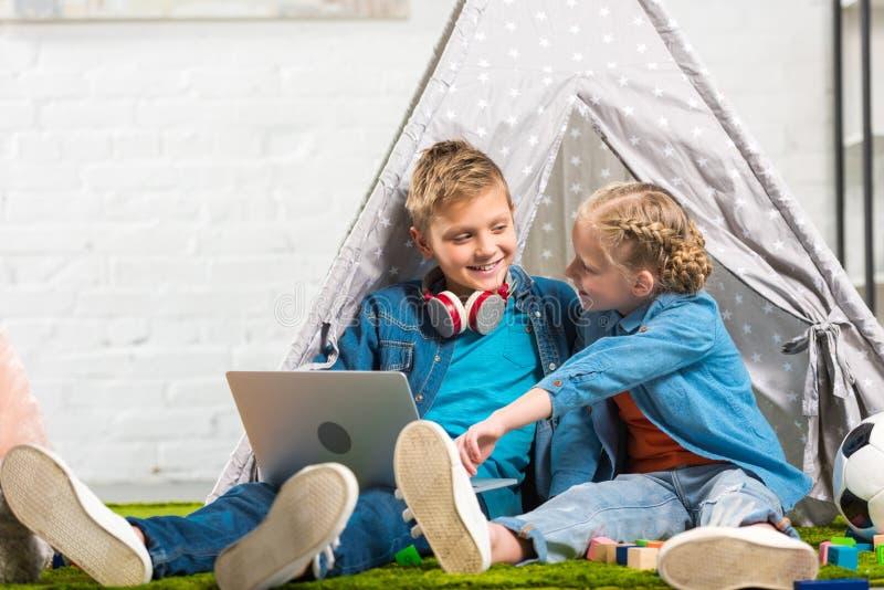 指向膝上型计算机屏幕的孩子有耳机的微笑的兄弟在脖子靠近帐篷 库存照片