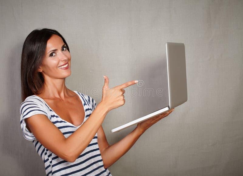 指向膝上型计算机的吸引人妇女,当站立时 免版税库存图片