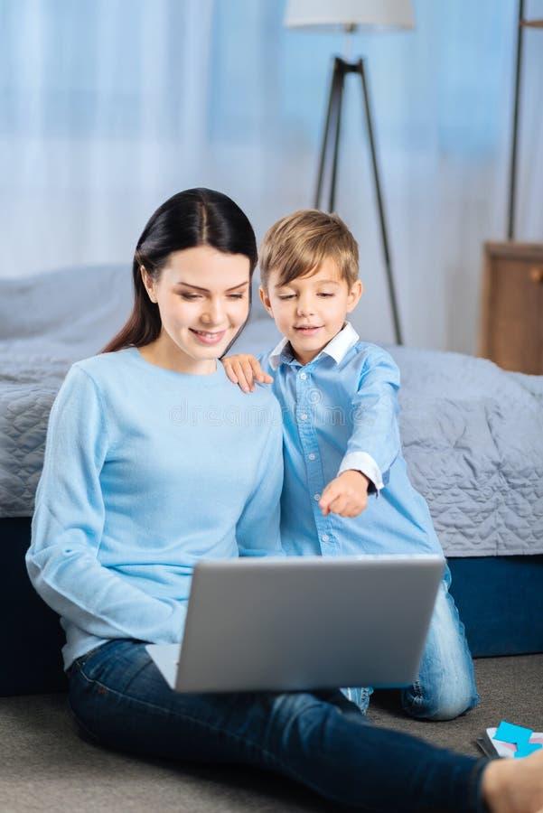 指向膝上型计算机的快乐的男孩,当观看与母亲时的动画片 免版税库存照片
