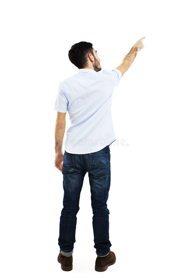指向衬衣和牛仔裤的年轻人后面看法  免版税库存照片