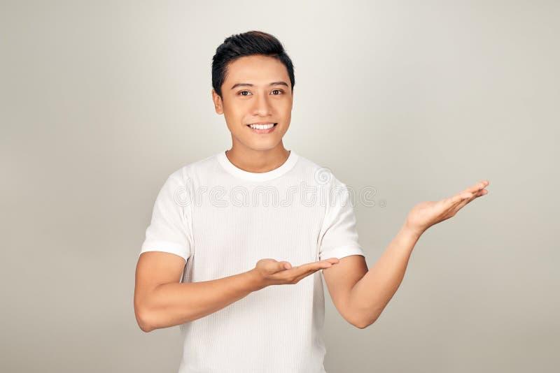 指向边的年轻帅哥用手和开放棕榈,提出广告微笑愉快和确信 库存图片