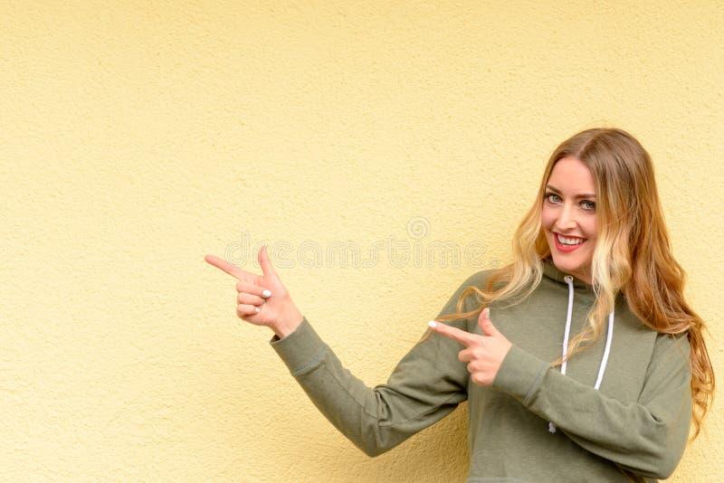 指向边的被激发的相当白肤金发的妇女 免版税库存照片