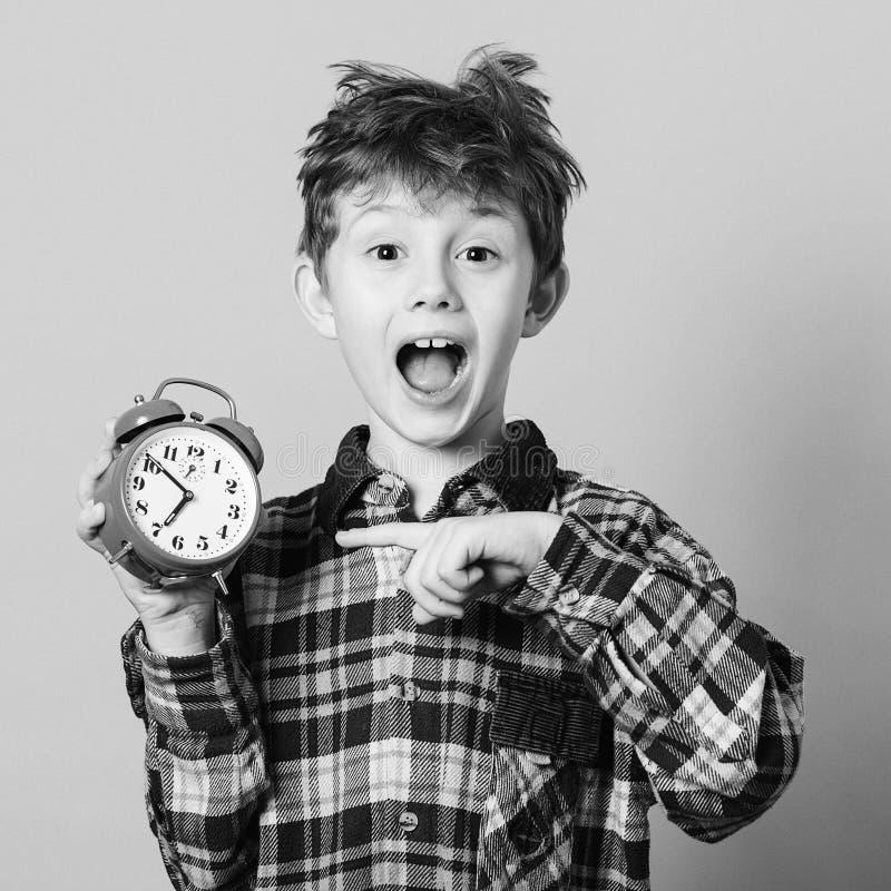 指向闹钟的滑稽的孩子 激动的男孩在学校前睡过头了 回到学校的孩子 查出在黄色 教育和 库存图片