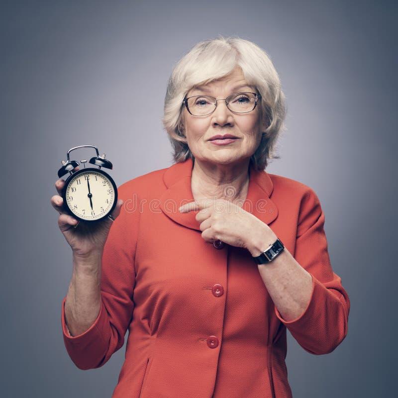 指向闹钟的资深夫人 库存图片