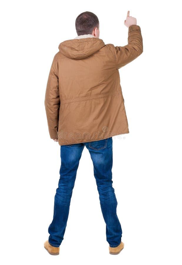 指向附头巾皮外衣的年轻人后面看法  库存照片