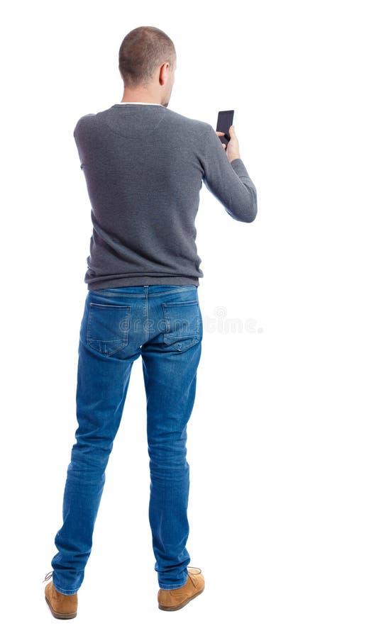 指向年轻人后面看法谈话在手机 免版税库存照片