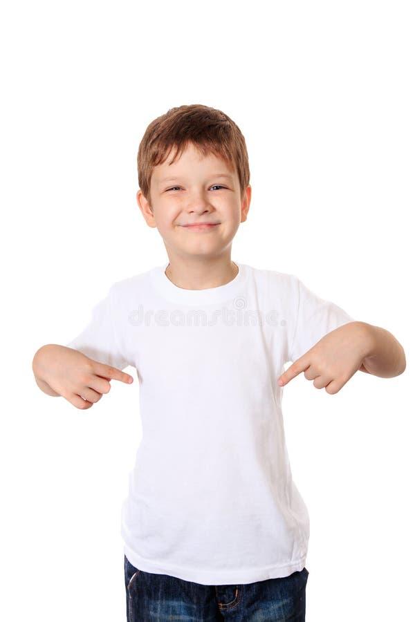 指向他的在一件空白的T恤杉, plac的愉快的小男孩手指 库存照片
