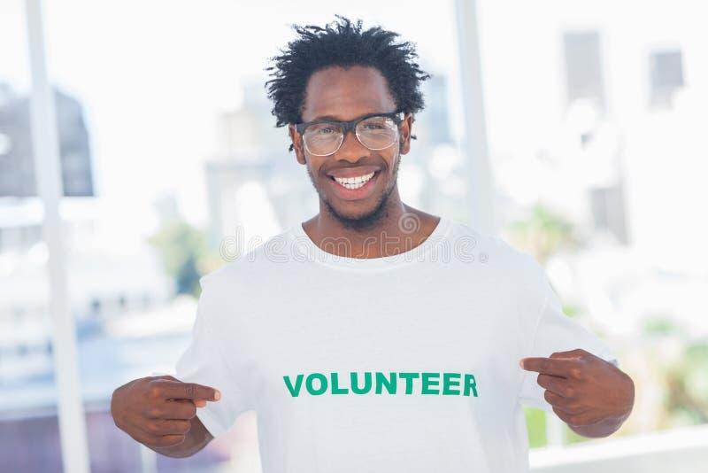 指向他的志愿T恤杉的英俊的人 图库摄影