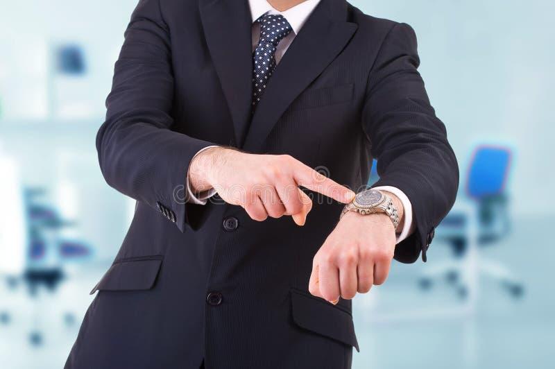 指向他的手表的商人。 免版税库存照片