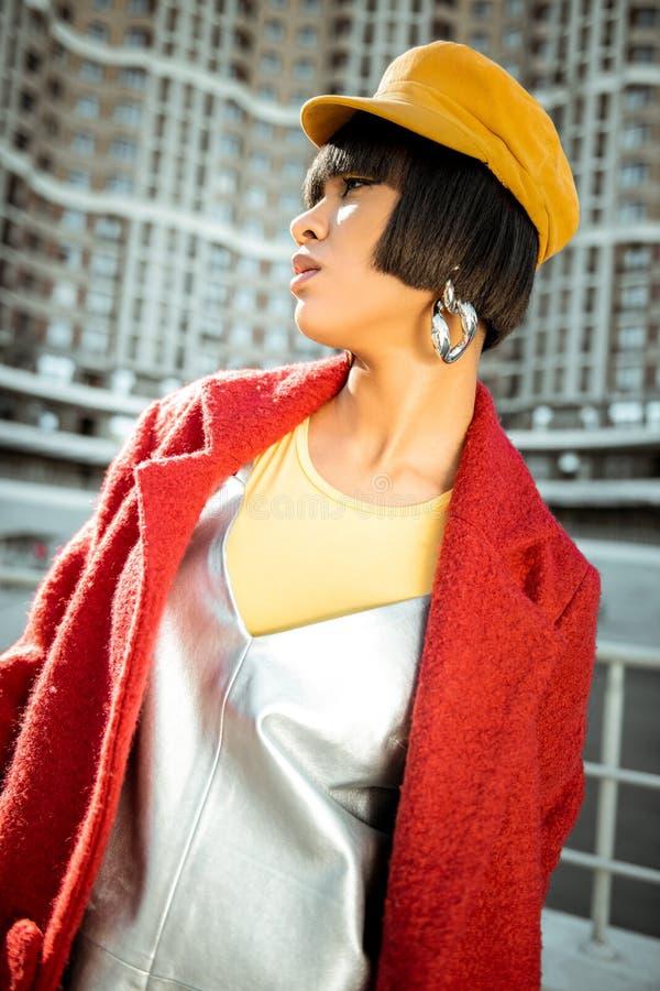 指挥她的眼睛的黄色帽子的混合的族种女朋友  免版税库存图片