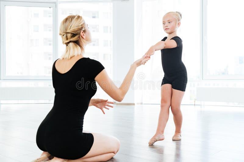 指挥小逗人喜爱的芭蕾舞女演员的芭蕾辅导员在舞蹈实践期间 库存图片