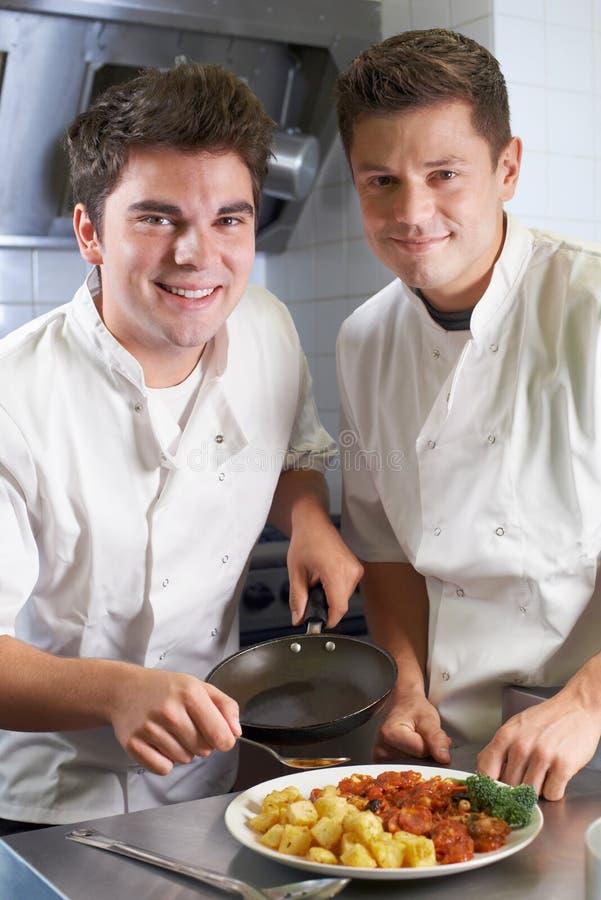 指示实习生的厨师画象在餐馆厨房里 免版税库存图片