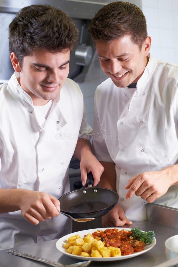 指示男性实习生的厨师在餐馆厨房里 免版税库存图片
