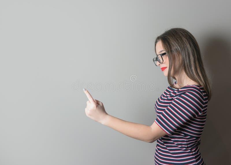 指责某人的年轻女人指向与在灰色背景的手指 库存照片