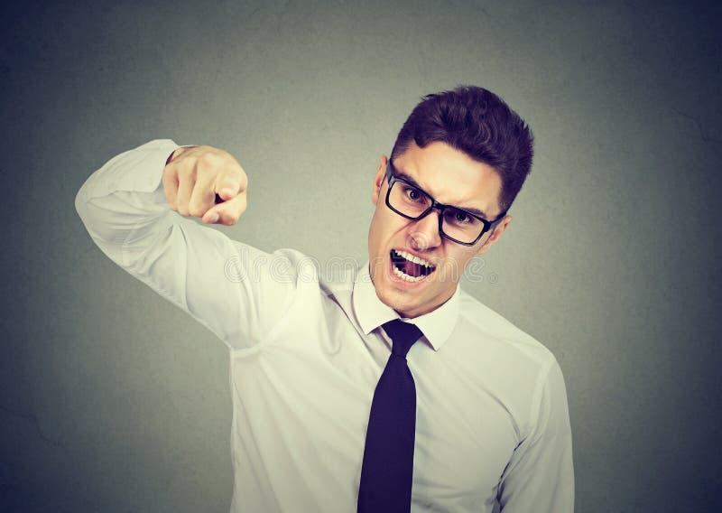 指责某人的恼怒的年轻商人 免版税库存图片