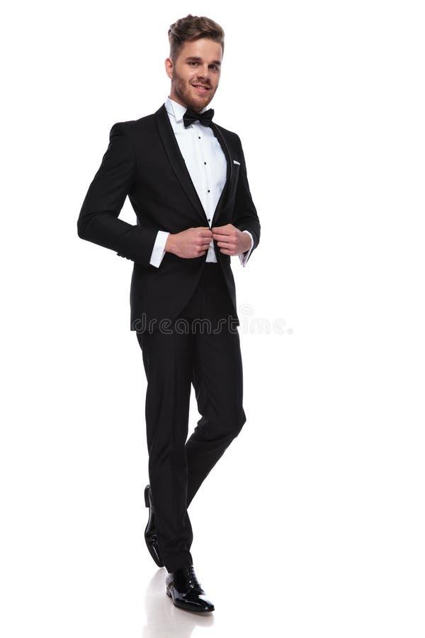 按他的无尾礼服的微笑的年轻新郎 免版税库存图片