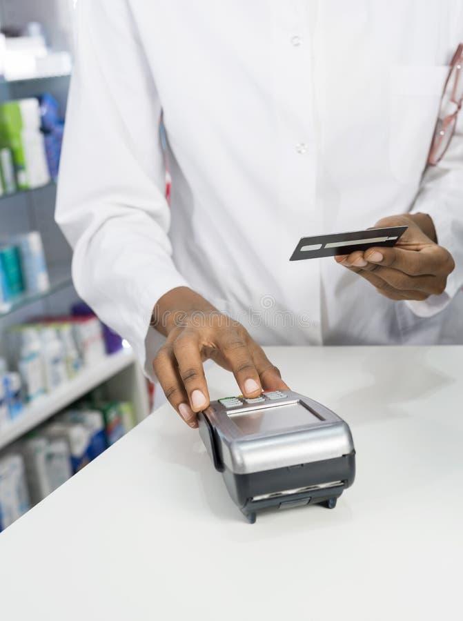 按卡片阅读机的按钮药剂师在柜台 免版税库存图片