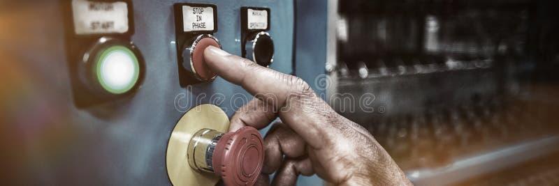 按在控制板的工厂劳工的手一个红色按钮 免版税库存图片