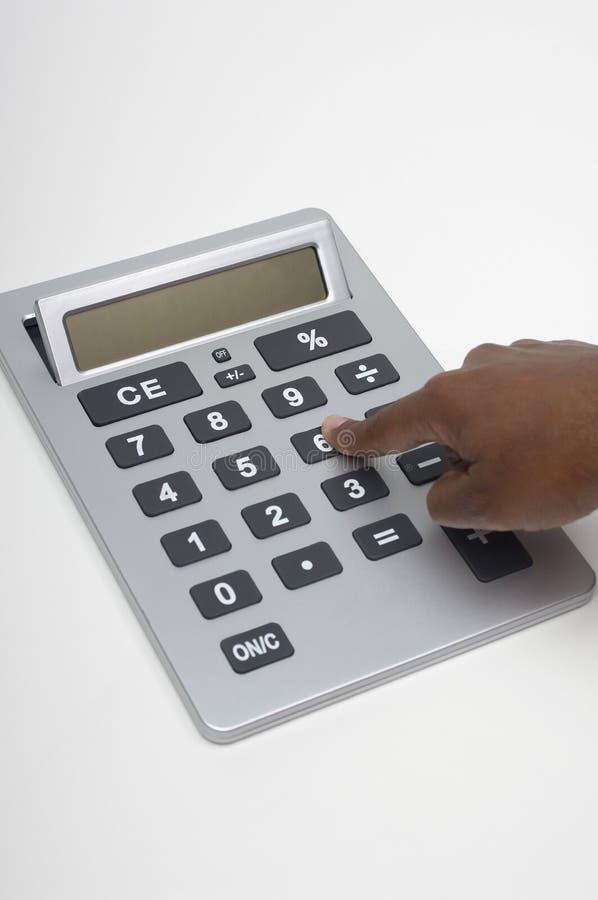 按在数字式计算器的手指特写镜头键 免版税库存图片