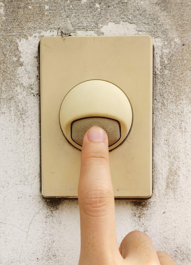 按在老门铃开关的手指 免版税库存图片