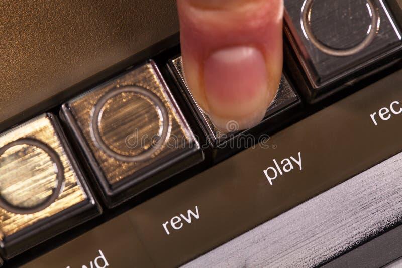 按在葡萄酒音乐播放器的手指减速火箭的戏剧按钮 库存照片