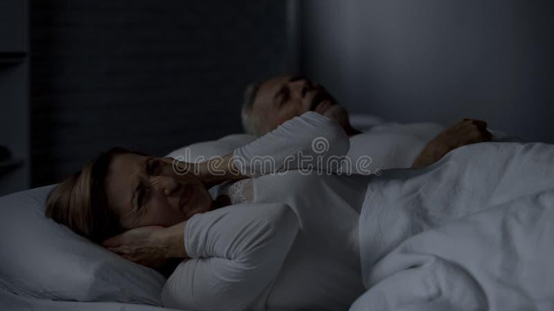 按手的年迈的夫人反对耳朵在床上由于响亮地打鼾的丈夫 免版税库存照片