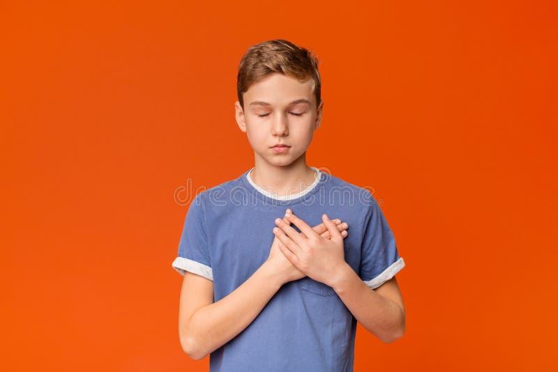 按手的敏感十几岁的男孩对是的胸口感恩的 图库摄影